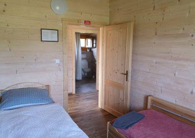 Pokoj ve velké chatě a sociální zařízení ve velké chatě přes chodbičku.